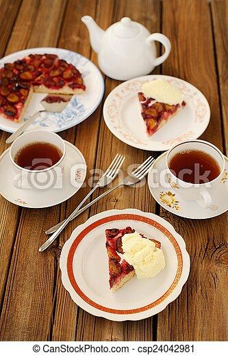 Upside down plum pie with ice-cream and black tea - csp24042981