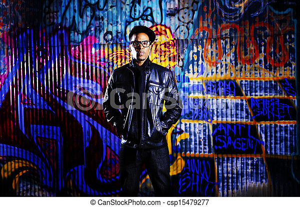 urban man in front of graffiti wall. - csp15479277
