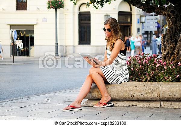 Retrato de una atractiva mujer rubia con tablet en el fondo urbano - csp18233180