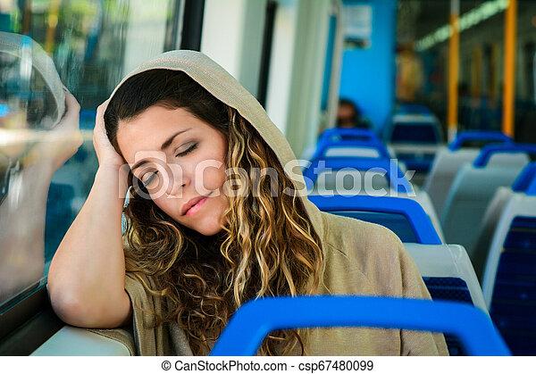 Una mujer urbana durmiendo en un tren viaja al lado de la ventana. - csp67480099