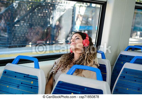 Una mujer urbana durmiendo en un tren viaja al lado de la ventana. - csp71850878