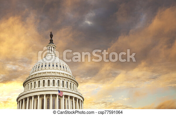 US Capitol dome with American flag and dramatic sky behind - csp77591064