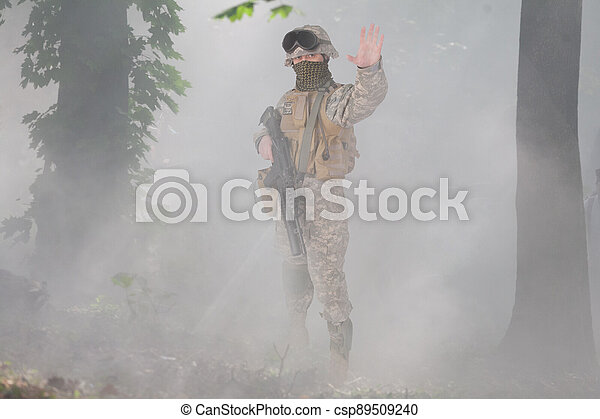 US soldier with assault rifle scouting in the foggy forest - csp89509240