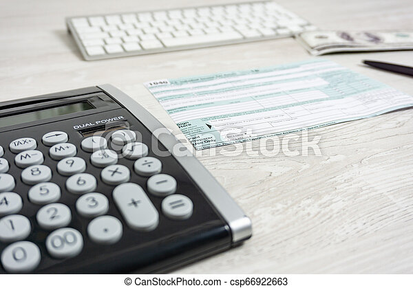 form 1040 business income  US tax form next to computer keyboard, calculator and tax form 14. tax  form us business income office hand fill concept