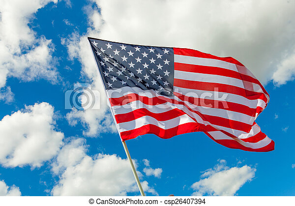 USA flag and cumulus clouds behind it - csp26407394