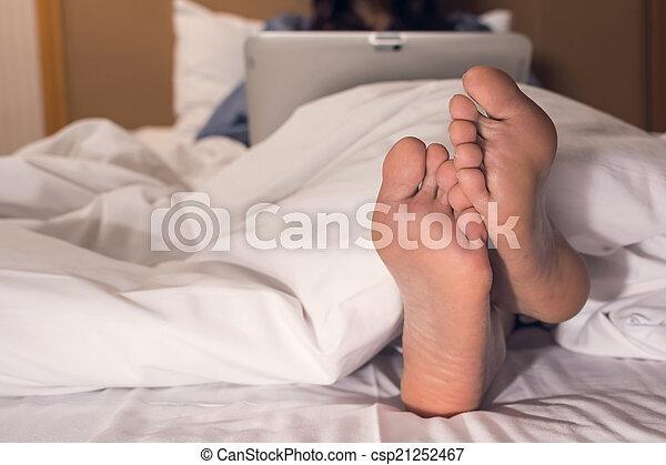 Mujer usando portátil en la cama - csp21252467