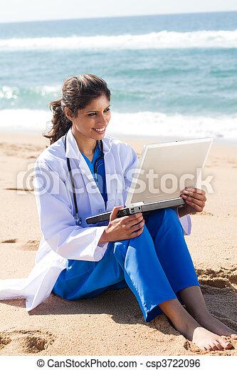 Bonita enfermera usando portátil en la playa - csp3722096