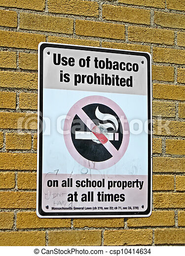 use of tabacco prohibited in all schools as message on sigbboard on brick wall, health details - csp10414634