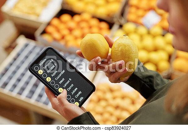 Using checklist on smartphone in supermarket - csp83924027