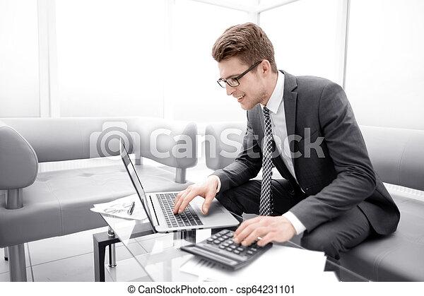 Un joven hombre de negocios usando calculadora y portátil - csp64231101
