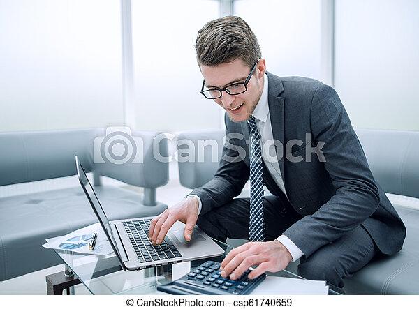 Un joven hombre de negocios usando calculadora y portátil - csp61740659