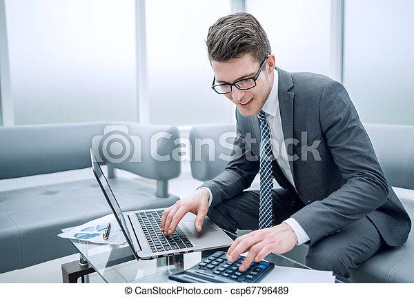Un joven hombre de negocios usando calculadora y portátil - csp67796489