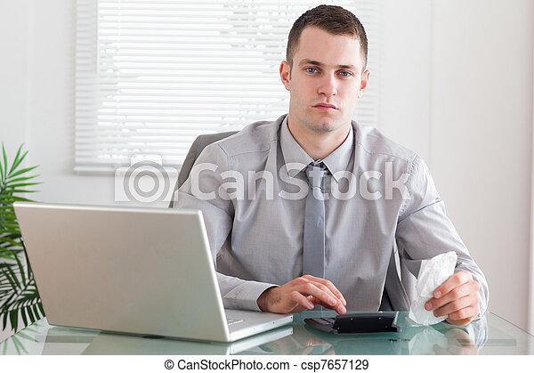 Hombre de negocios usando su calculadora - csp7657129