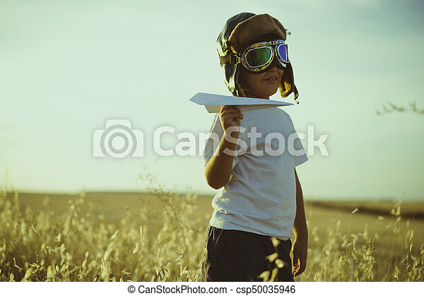 Vacation, Boy playing to be airplane pilot, funny guy with aviator cap and glasses, carries in his hand a plane made of paper - csp50035946