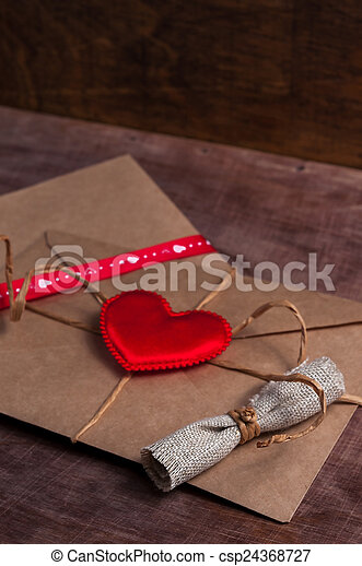 Valentine's day. Envelope with red hearts on Brown wooden background. - csp24368727