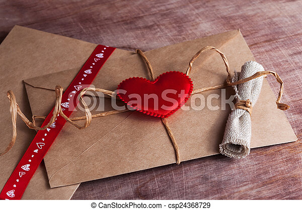 Valentine's day. Envelope with red hearts on Brown wooden background. - csp24368729