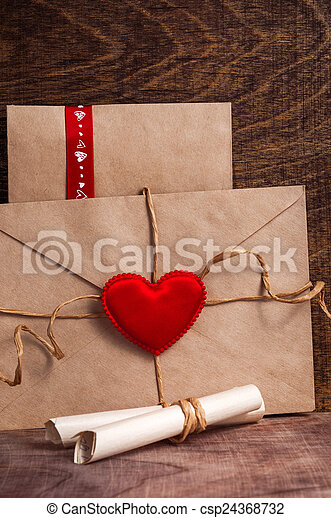 Valentine's day. Envelope with red hearts on Brown wooden background. - csp24368732