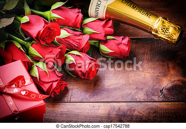 Valentine's setting with red roses, champagne and gift - csp17542788