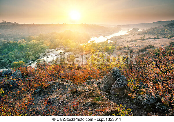 Valley with mountain river in the rocky shores at sunset - csp51323611