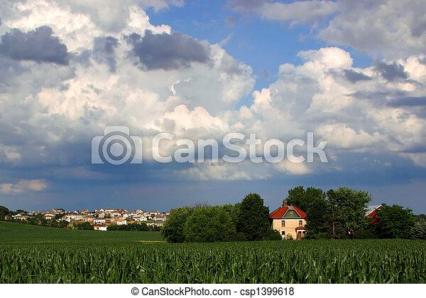Vanishing Farmland (cornfield and house with housing development) - csp1399618