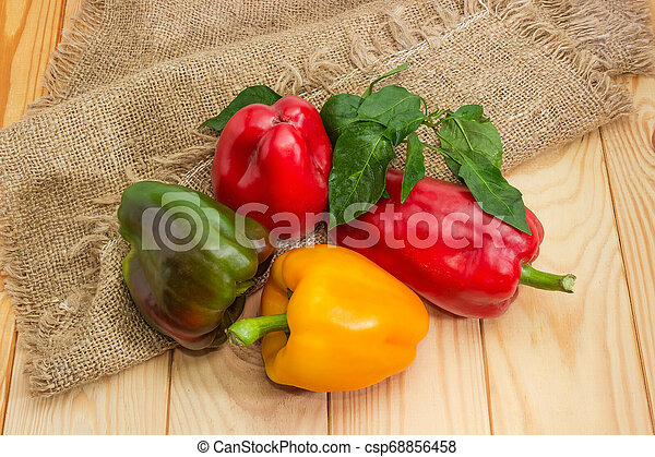 Varicolored bell peppers with leaves on the wooden rustic table - csp68856458