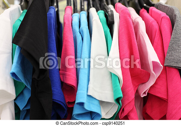 Variety of multicolored casual clothes in shop; T-shirts hanging on hangers - csp9140251