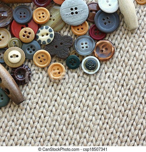 Variety of Vintage Buttons Scattered on Knit Fabric Background - csp18507341