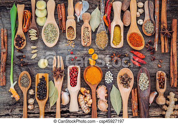 Various of spices and herbs in wooden spoons - csp45927197