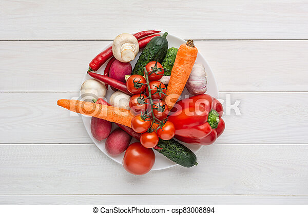 Various raw vegan vegetables on a white plate and wooden background with blank space around. Zucchini, cucumber, chili pepper, mushrooms, tomatoes, cauliflower, carrots. - csp83008894