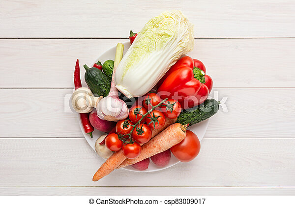 Various raw vegetables on a white plate and wooden background with blank space around. Zucchini, cucumber, chili pepper, mushrooms, tomatoes, cauliflower, lettuce, carrots. - csp83009017