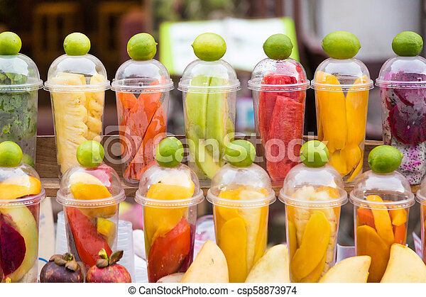 Various tropical fruits prepared in cups for making mixed fruit smoothie, waiting for customers - csp58873974