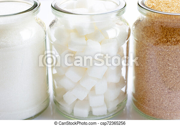 Various types of sugar in a glass jar on white - csp72365256