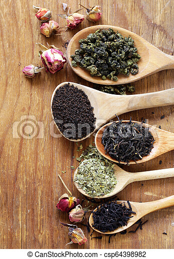 various types of tea in a wooden spoon - csp64398982