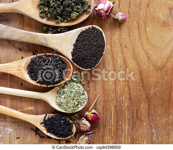 various types of tea in a wooden spoon - csp64398959