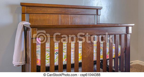 Varnished wooden crib inside a nursery - csp61044388