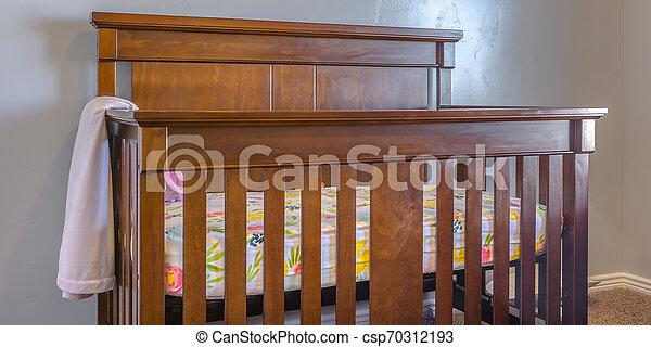 Varnished wooden crib inside a nursery - csp70312193