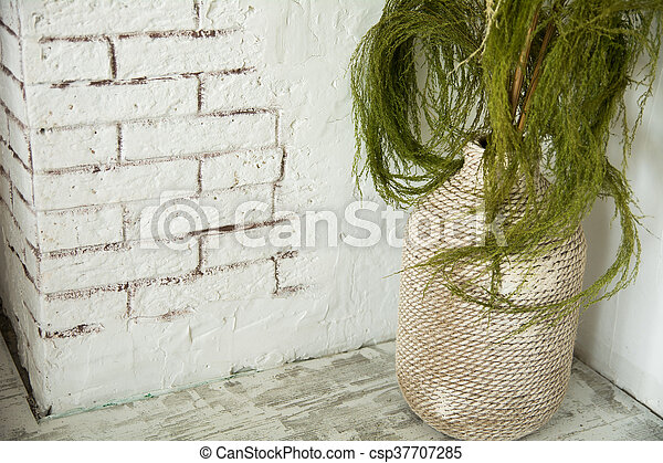 Vase with green branches on the floor - csp37707285