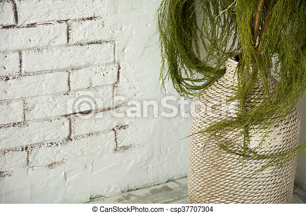 Vase with green branches on the floor - csp37707304