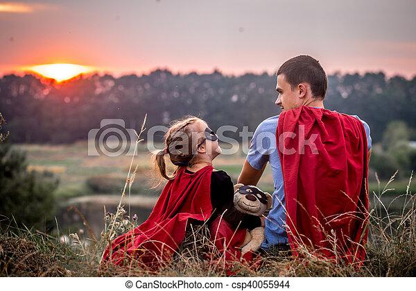 Kleines Mädchen mit Dad, gekleidet in Superhelden, glückliche Familie - csp40055944