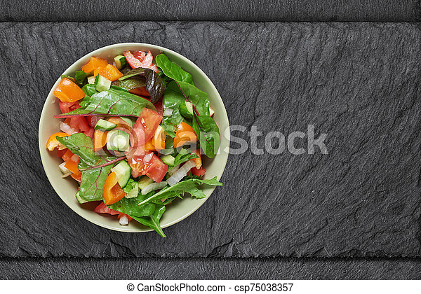 vegetable salad in a bowl on stine table. Top view - csp75038357