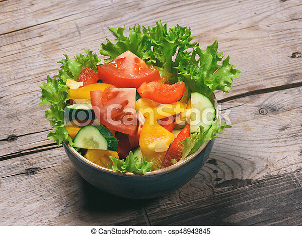vegetable salad in a bowl on wooden table - csp48943845
