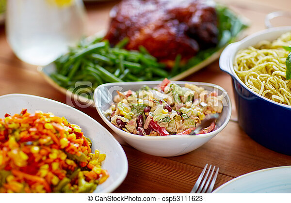 vegetable salad in bowl and other food on table - csp53111623