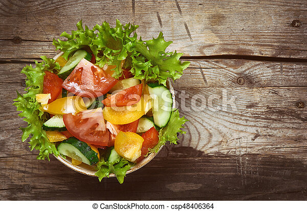 Vegetable salad in bowl on wooden table - csp48406364