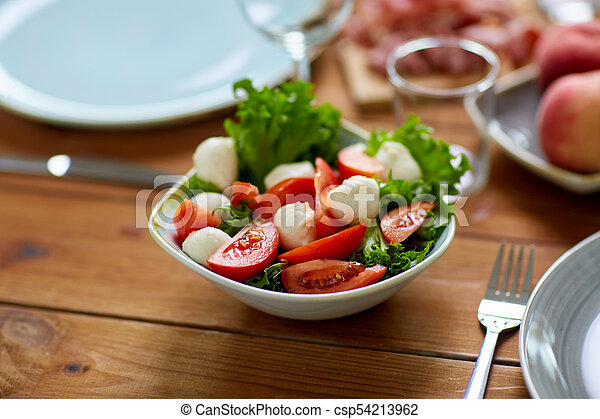 vegetable salad with mozzarella on wooden table - csp54213962