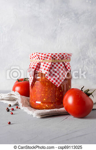 Vegetable sauce adjika with tomatoes, garlic, bell peppers in jar on light background. - csp69113025