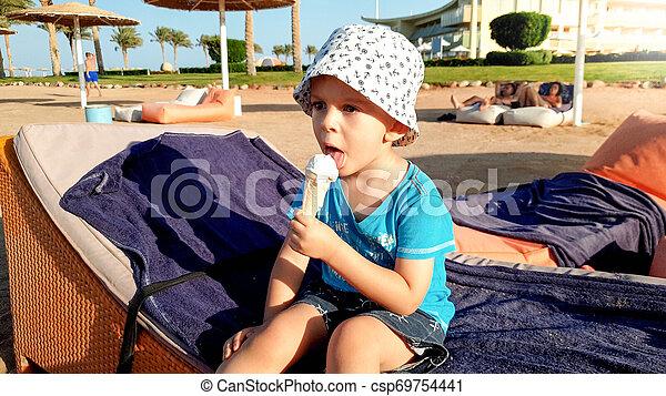 Retrato de adorable niño de 3 años sentado en la playa y comiendo delicioso helado dulce. Niños relajándose en las vacaciones de verano en la playa - csp69754441