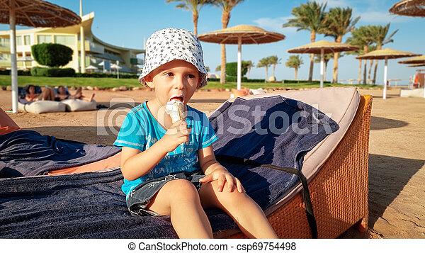 Retrato de adorable niño de 3 años sentado en la playa y comiendo delicioso helado dulce. Niños relajándose en las vacaciones de verano en la playa - csp69754498