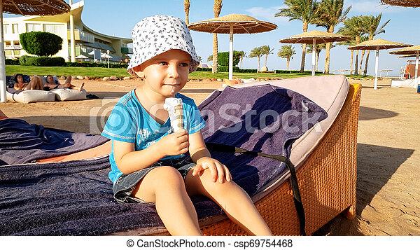 Retrato de adorable niño de 3 años sentado en la playa y comiendo delicioso helado dulce. Niños relajándose en las vacaciones de verano en la playa - csp69754468