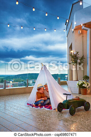 Los niños felices se esconden en una peluca hecha a mano de una repentina lluvia de verano en el patio, jugando juntos - csp69807471