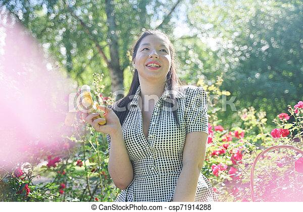 Chica asiática descansando en el verano en el parque con el intenso calor del sol - csp71914288